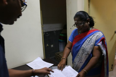 Dr. Ramu and Ms. Shanti (trainer) review the completed quizzes.