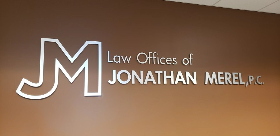 image of brushed metel lawyer sign on brown wall.
