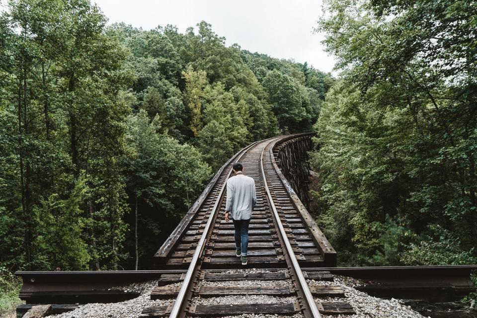 Image of man walking alone on the railtracks