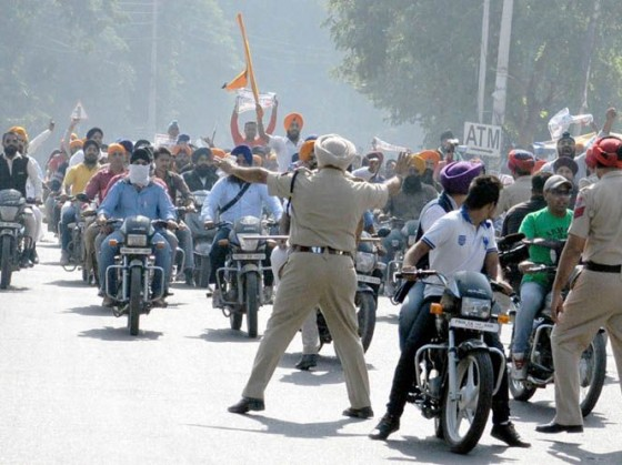 Police personnel trying to stop youth who were taking out a march in Jalandhar city