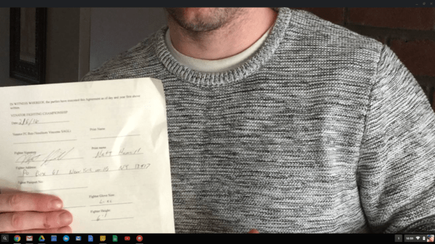 Matt Hamill holds up his contract with Venator Fighting Championship in Milan, Italy.