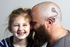 Charlotte Campbell age 6 with her dad Alistair who had a cochlear implant tattooed on his head to support Charlotte who is deaf. Photo / Dean Purcell, NZ Herald