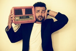 Vaibhav Kothari is holding a radio on his shoulder and posing for professional shot.
