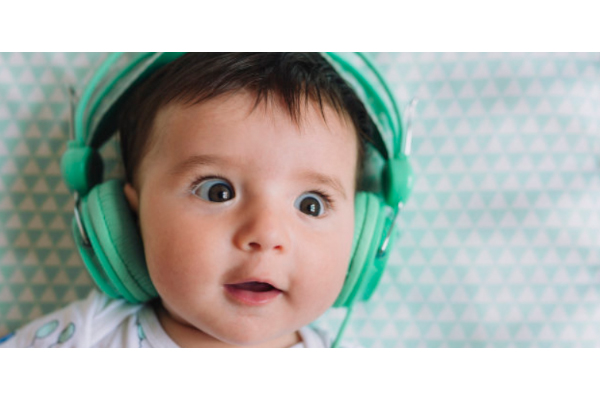 A baby with green headphones