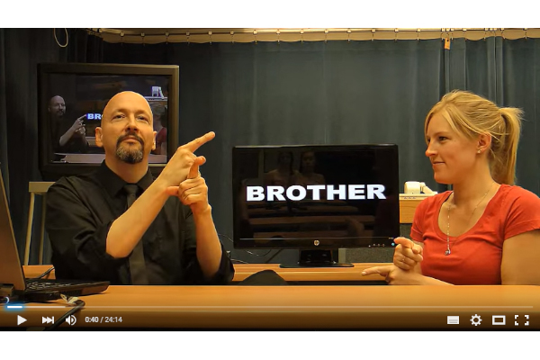 """2 people sitting next to each other with a word """"brother"""" in the back"""