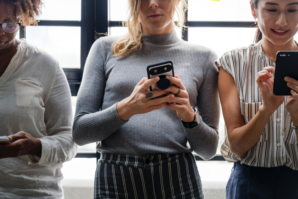 How to find blog post topics people actually want to read feature image - three women staring intently at their phones in a line against a window.