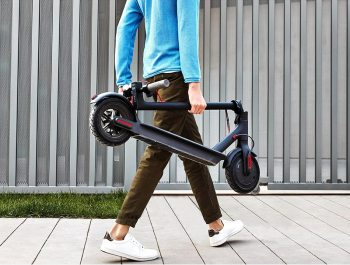 young man carrying Xiaomi electric scooter