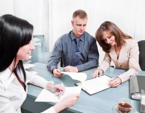 AA Rental Property couple-signing-papers-in-office-with-black-haired-female-agent
