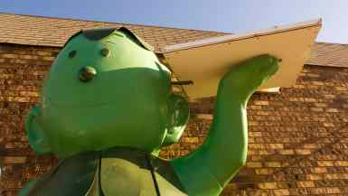 Fiberglass Little Green Sprout statue holds a beer and a pizza box outside of a gas station in Blue Earth, Minnesota.