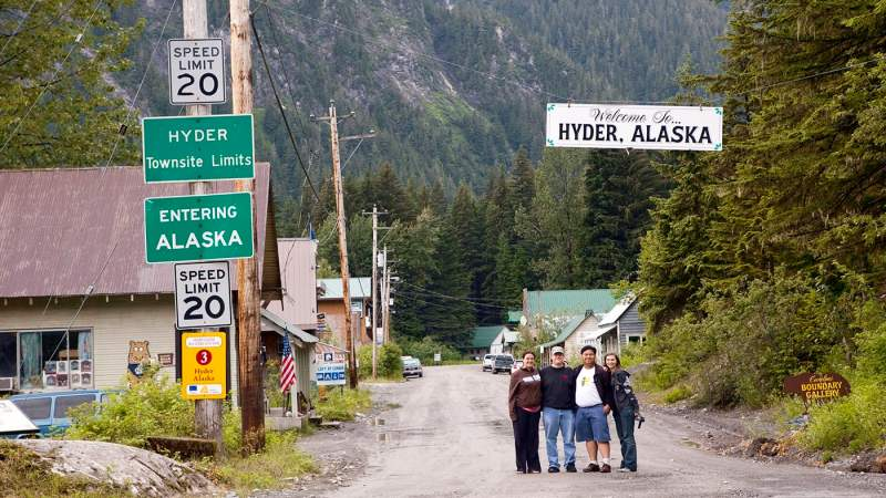Road trippers in front of the Welcome to Hyder, Alaska sign.