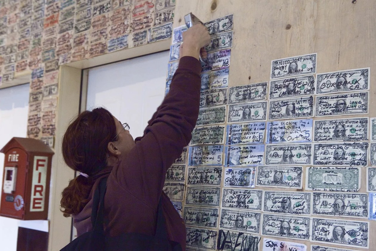 Rose staples our signed dollar to the wall of the Glacier Inn in Hyder, Alaska.