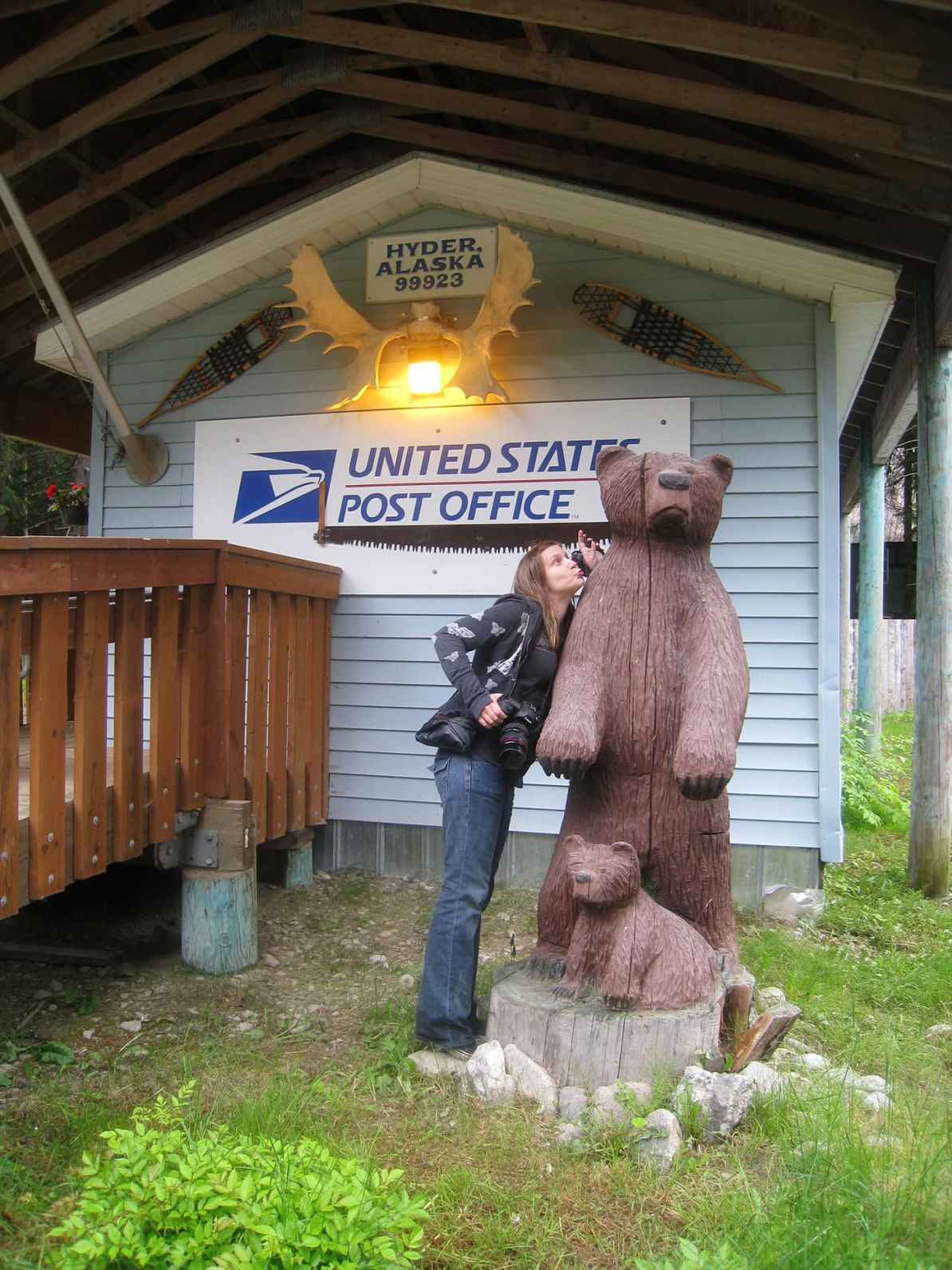 Val kisses the wooden carved bear and cub at the Hyder, Alaska Post Office.