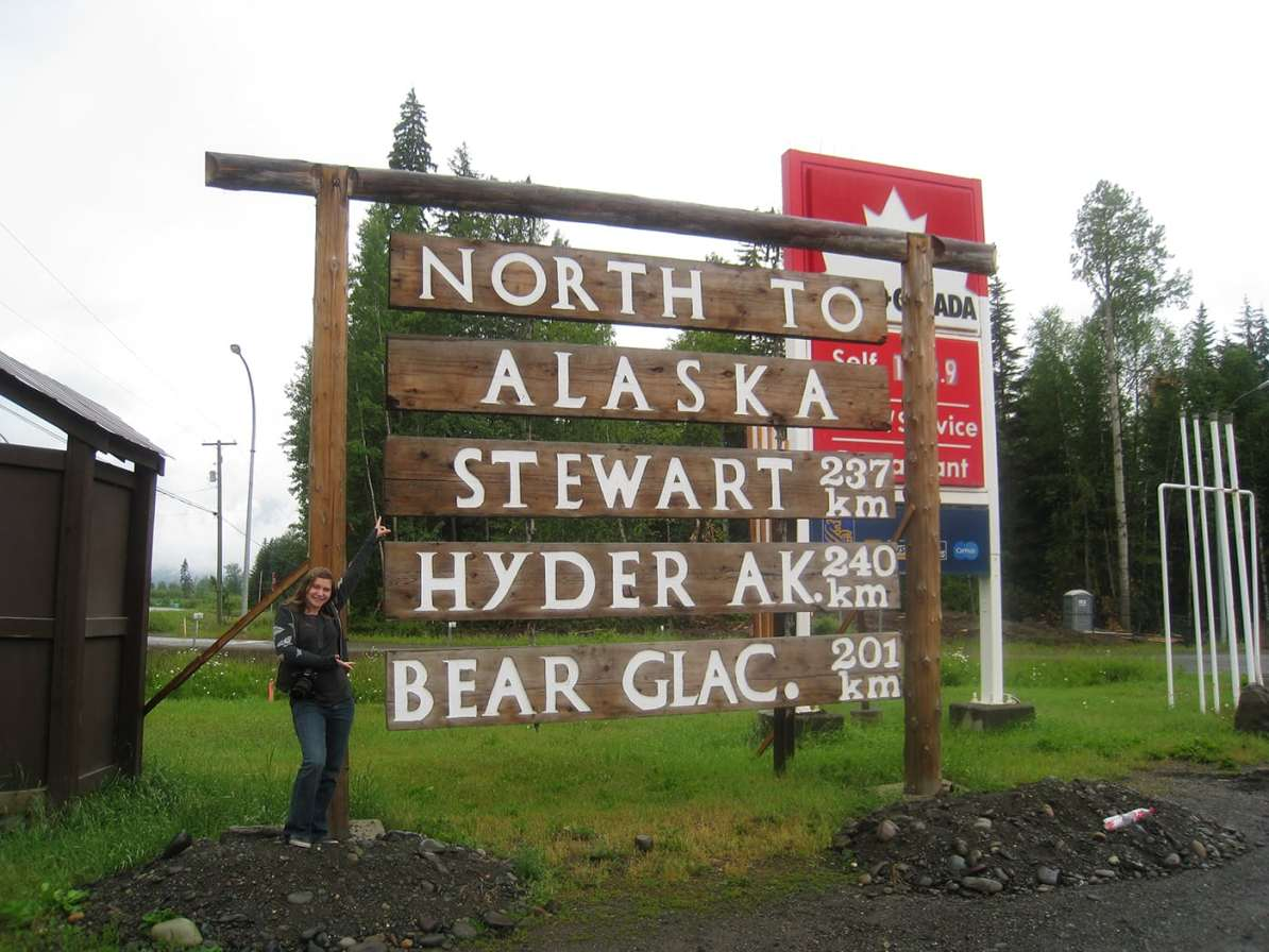 Val with the North to Alaska, Stewart, Hyder, Bear Glacier sign in Kitwanga,British Columbia, Canada.