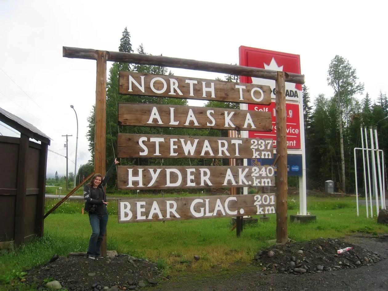 Val with the North to Alaska, Stewart, Hyder, Bear Glacier sign in Kitwanga,British Columbia, Canada.