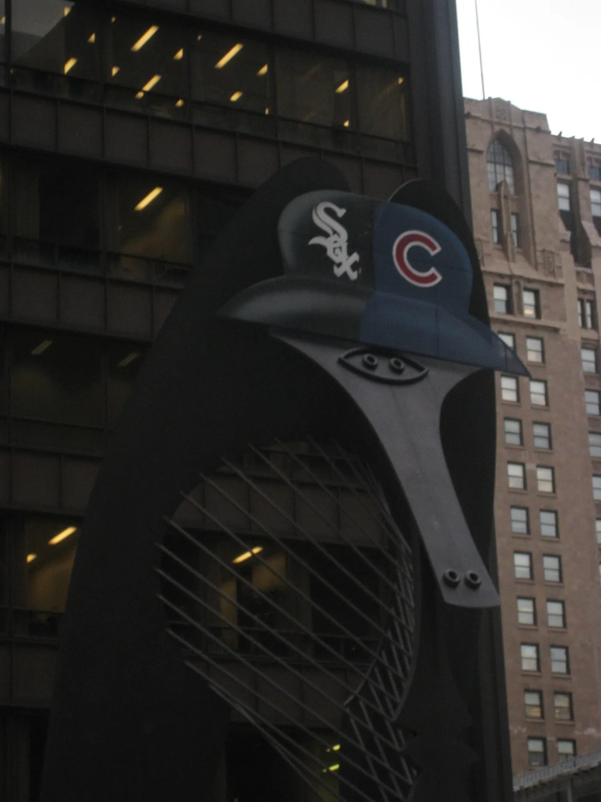 The Chicago Picasso outside of the Daley Center wearing a Cubs/White Sox hat.