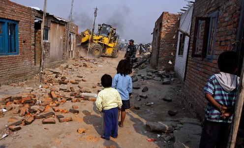 children watching demolition of slum home