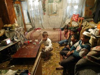Children in an Uzbek household enjoying football match on television