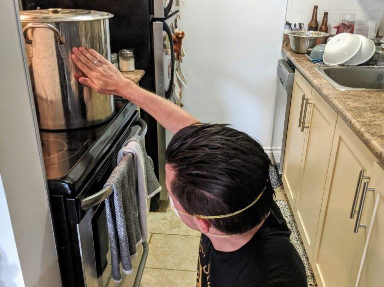 man touches brew kettle