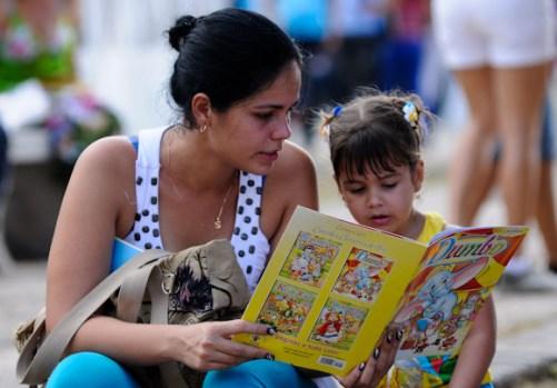 Una joven lee junto a su nina un libro de cuentos recien comprado en la Feria del Libro, el viernes 22 de febrero de 2013, La Habana. FOTO: Calixto N. Llanes (CUBA)