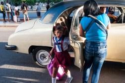 Niña junto a su madre se bajan de un auto antiguo (almendrón) a la entrada de su escuela el primer día de clases del nuevo curso escolar 2015-2016 el martes 1 de septiembre de 2015. FOTO de Calixto N. Llanes/Juventud Rebelde (CUBA)