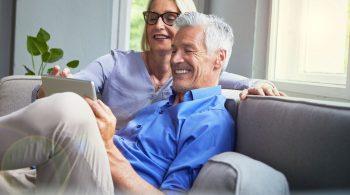 Älteres Paar auf der Couch checkt die Aktien