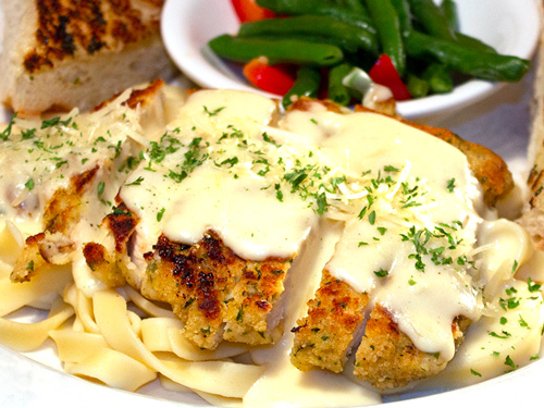Photo of chicken alfredo served with garlic bread and vegetables