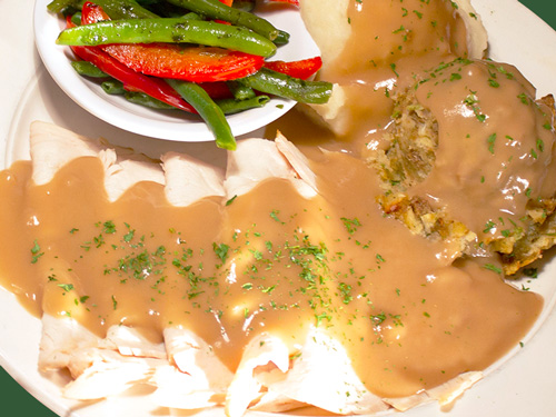 Photo of sliced turkey served with gravy, mashed potatoes, and vegetables