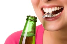 woman opening bottle with teeth