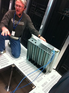 A photo of an intelligent data center floor tile with remotely controlled mechanical louvres to control air flow.
