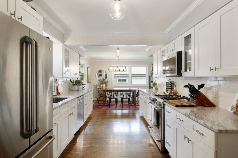 Remodeled 1950's kitchen, white cabinets, carrara marble countertops, subway tile backsplash, open concept kitchen / Sima Spaces