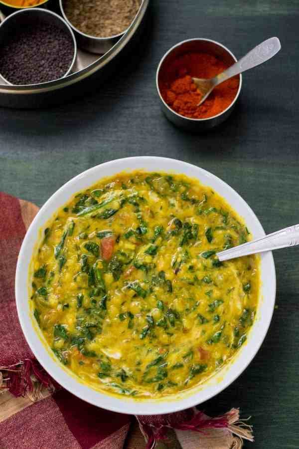 This mildly spiced, creamy version of Spinach and Tomato Dal (Dal Palak) makes for a delicious main course over hot cooked rice; it can also be served as a side dish.