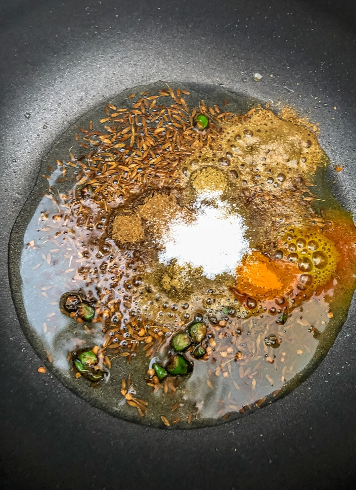 Green chilies, coriander, cumin, turmeric powder and salt added to the tempering