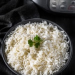 Basmati rice served in a black bowl placed in front of Instant Pot