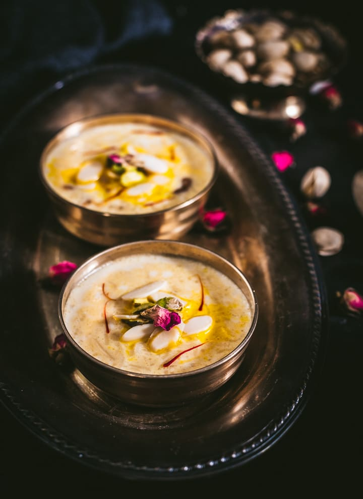 Two small bowls of creamy rice kheer on a silver platter on the left of the picture with mixed nuts in a small bowl of the right of the picture all on a black table cloth with almond slivers scattered on top.