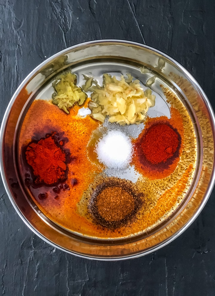 The spices used to make the tandoori salmon marinade in the base of the instant pot, unstirred.