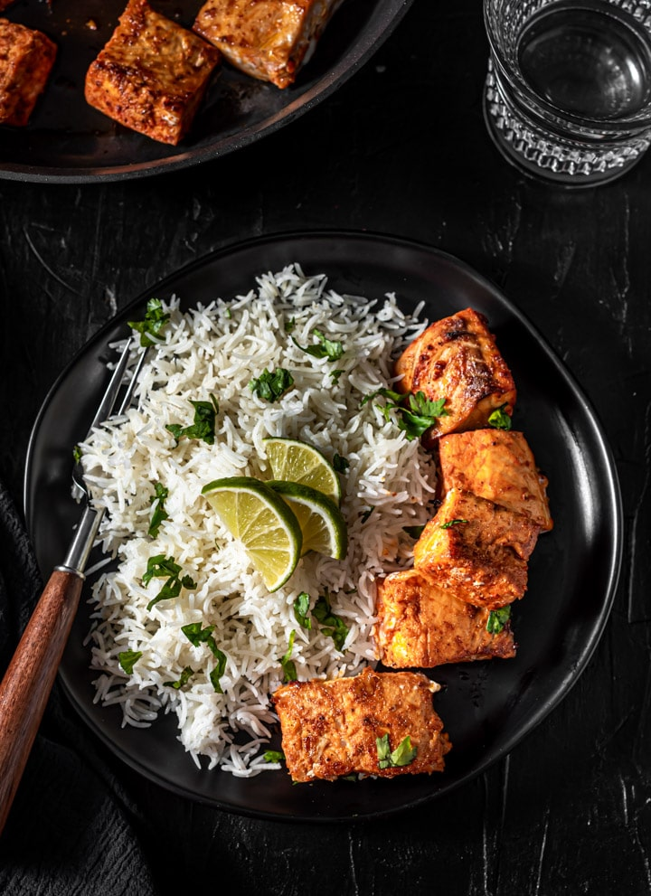 A balck plate with tandoori salmon on the right side and rice on the left side with a brown handled fork.