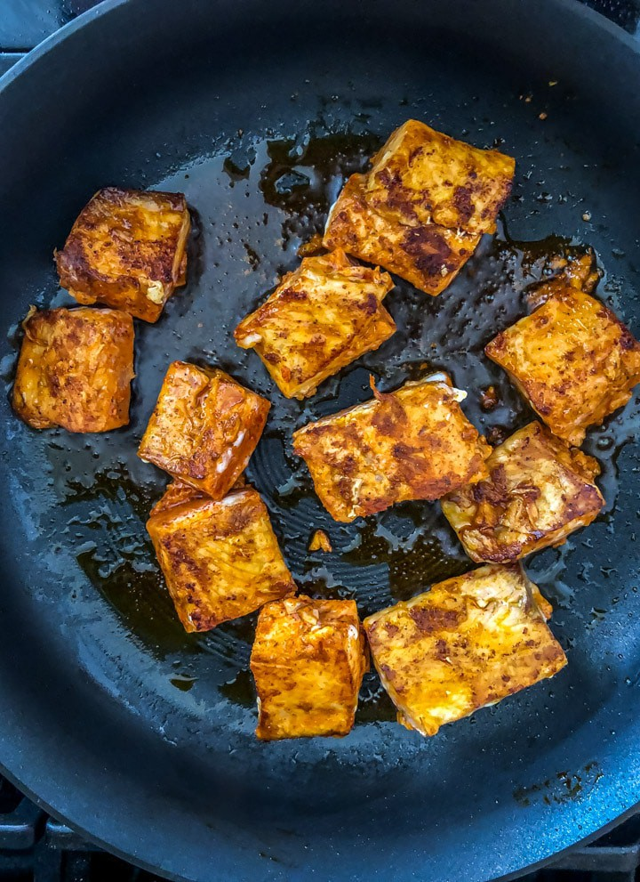 Tandoori salmon pieces cooking on the stove top in a non-stick pan with oil.