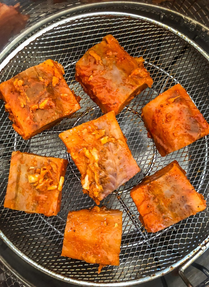 7 pieces of tandoori salmon cut into squares, resting on the greased Mealthy CrispLid tray. They are arranged in a circle with one piece in the middle and 6 around the edges.