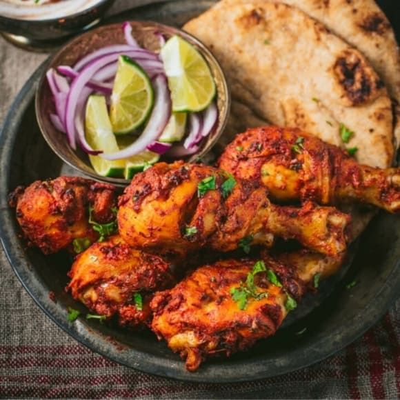 Tandoori chicken served with naan and sliced limes and onions