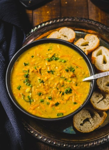Broccoli Cheddar Soup served in a black bowl accompanied by baguettes