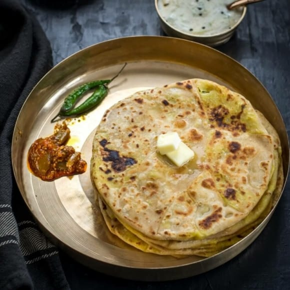 An overhead shot of Aloo paratha served with a dollop of butter, pickles and green chilies