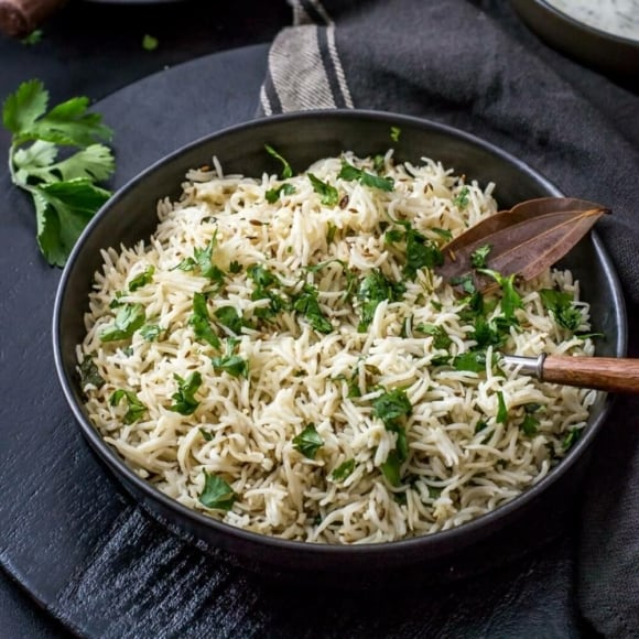 An overheat shot of cumin rice served in a black bowl
