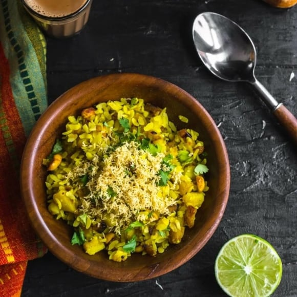 An overhead shot of Batata Poha in a brown bowl with a side of lime