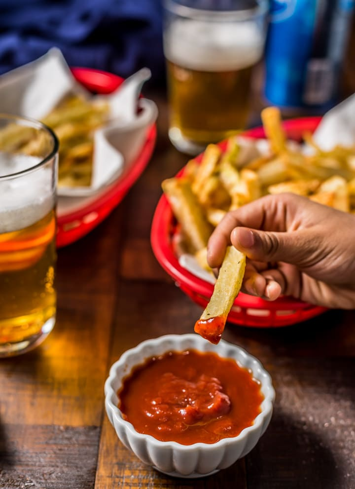 A hand dipping an air fryer french fry into a small bowl of ketchup with two red baskets filled with fries and two glasses of beer on a wooden table.