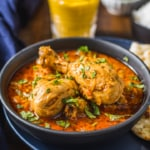 A close up shot of Indian curry chicken served in a gray bowl accompanied with naan and lassi