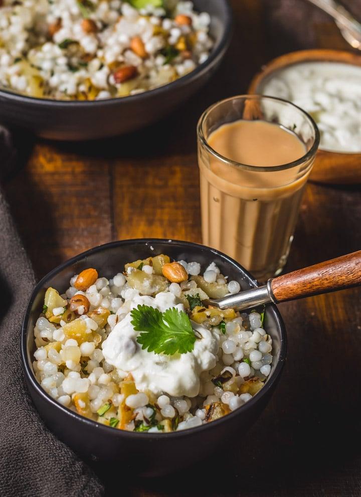 Sabudana khichdi served with a dollop of yogurt and accompanied with tea
