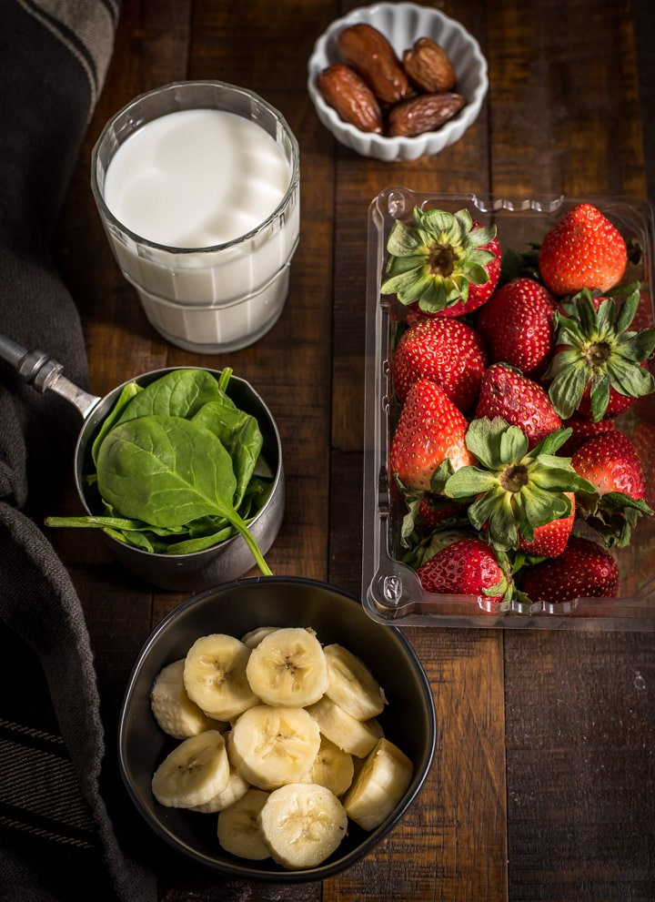 Strawberry Banana Spinach Smoothie Ingredients such as spinach, milk, banana, strawberry and dates are kept on a wooden surface