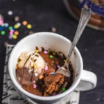 A white coffee mug with a chocolate mug cake inside topped with vanilla chocolate ice cream, sprinkles and chocolate sauce with a fork sticking out of the mug.