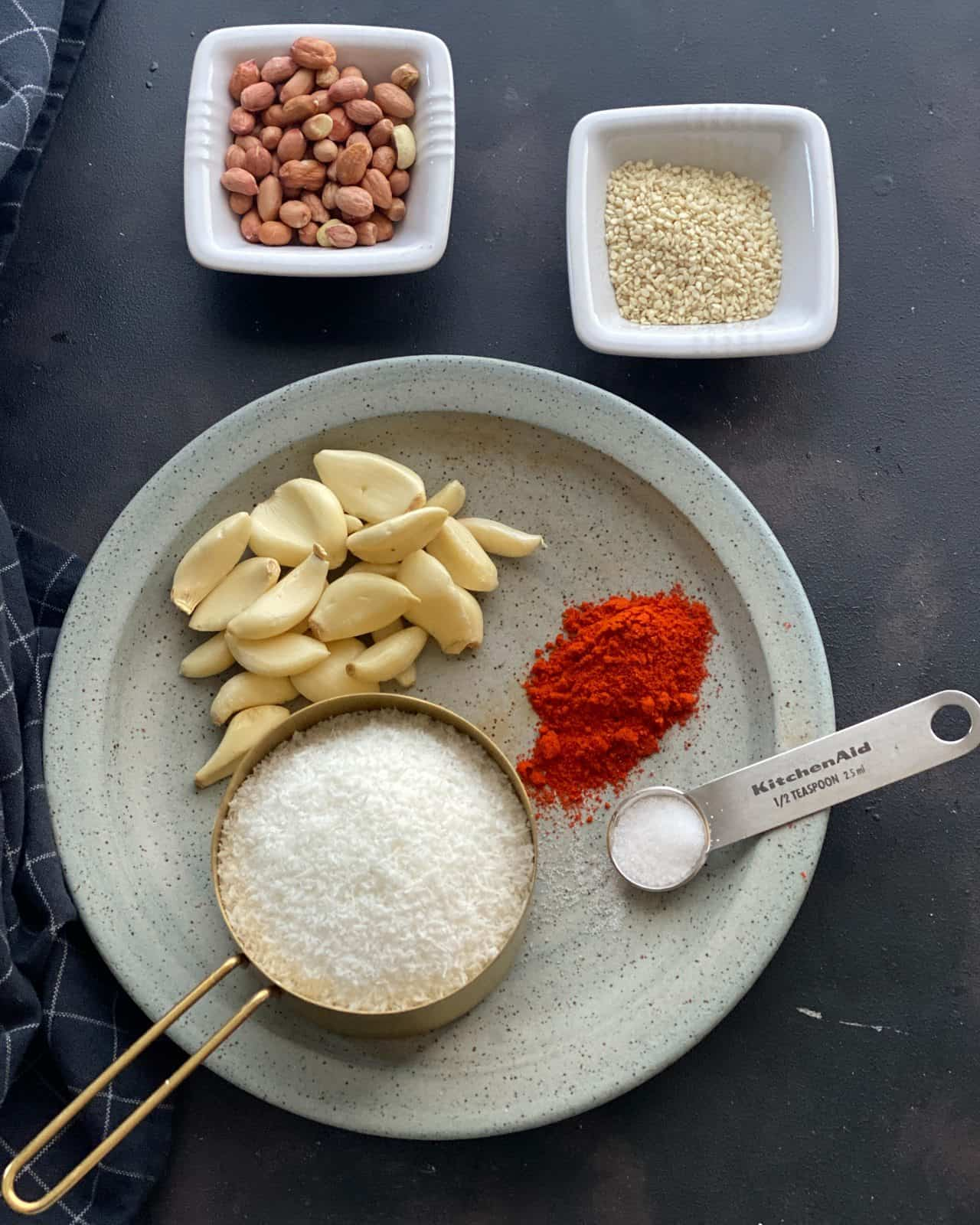 Ingredients for garlic chutney laid out in grey plate - desiccated coconut, chili powder, garlic cloves, salt. Sesame seeds and red skin peanuts are in separate bowls.