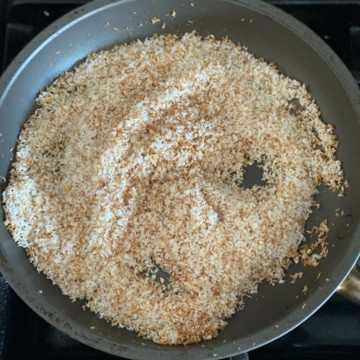 Desiccated coconut along with sesame seeds being roasted in a pan